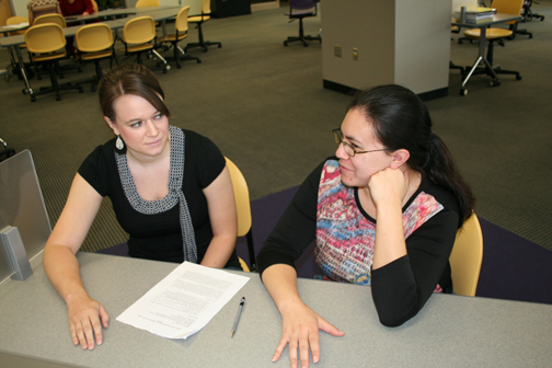 Photo by Zach Becker. At right, Bear Claw Writing Center tutor Sarah Viehmann, graduate student in English Composition and Rhetoric, gives writing tips for a class paper to senior Allison Bates, an English Education major.